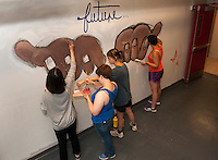 """Up With People cast members Ruiling Zhu, Kelani Schumann, Emily Axelsson and Jimena Silva work on their """"future"""" mural at Laconia High School as part of their community service project on Tuesday morning.  (Karen Bobotas/for the Laconia Daily Sun)"""
