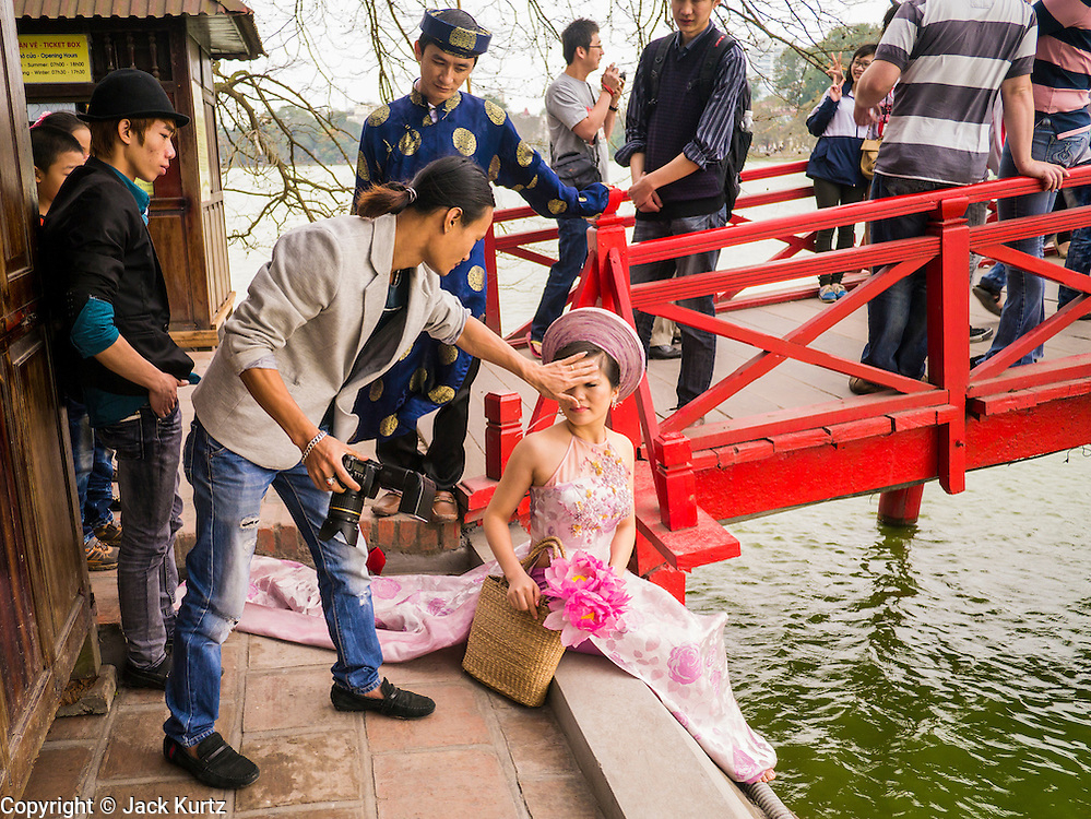 31 MARCH 2012 - HANOI, VIETNAM:   A photographer photographs a Vietnamese woman in Vietnamese formal wear outside of Ngoc Son Temple, which was reportedly built during the Tran Dynasty (ca 1225) in the Old Quarter of Hanoi, Vietnam. The temple is dedicated to Tran Hung Dao, a Vietnamese national hero who defeated an invading Mongol army in the 13th century.      PHOTO BY JACK KURTZ