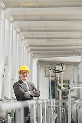 Young businessman standing with his arms crossed at geothermal power station, Bavaria, Germany