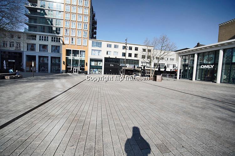 Nederland, Nijmegen, 6-4-2020 Plein44, een groot plein met winkels zoal s de Primark in de binnenstad, in het uitgstorven stadscentrum . Om te voorkomen dat groepen mensen dicht bij elkaar komen wordt door politie en boas extra surveillance gehouden . De terrassen zijn afgezet en gesloten met lint om duidelijk te maken dat daar niet in de zon gezeten mag worden . Foto: Flip Franssen