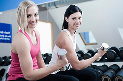 Two women in gym doing weight training