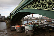House boats and barges moored at low tide on the River Thames underneath Battersea Bridge on 1st February 2020 in London, England, United Kingdom. Battersea Bridge is a five-span arch bridge with cast-iron girders and granite piers crossing the River Thames in London, England. It is situated on a sharp bend in the river, and links Battersea south of the river with Chelsea to the north.