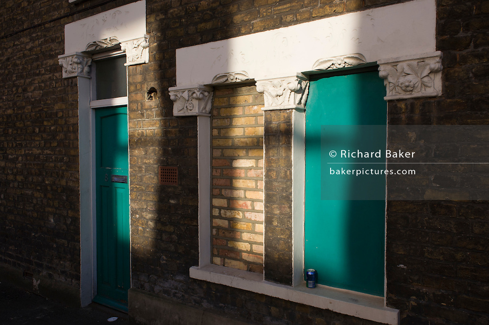 A half-bricked up and painted Victorian terraced house window.