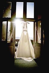 Sun shining through on to the beautiful Wedding Dress hanging up in the window at Eynsham Hall