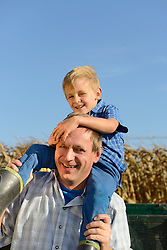 Father carrying his son on shoulders in cornfield, Bavaria, Germany