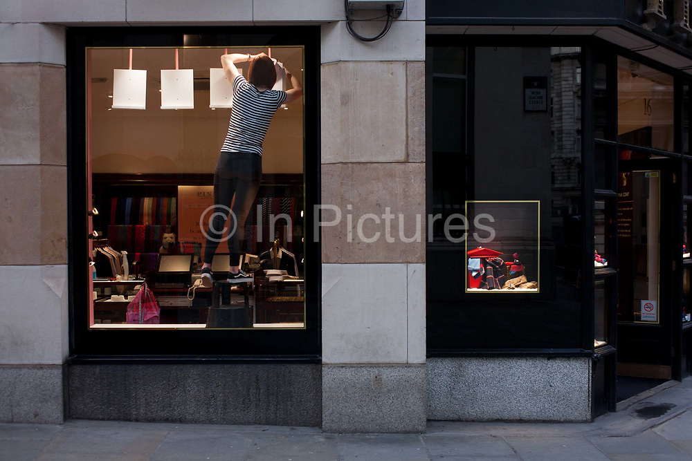 In a scene of rectangles, a shop worker balances while adjusting a new window display in a store, on 9th December 2016, in the City of London, England.