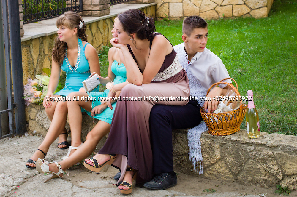 20150829  Moldova, Transnistria,Pridnestrovian Moldavian Republic (PMR) Dubushari.Friends of a bride a little bored with two champagne glasses and a bottle waiting for the newly weds ending their photo session in the park