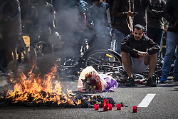 May 26, 2019 - Barcelona, Catalonia, Spain - A Glovo delivery boy is seen seated on his bike watching the backpacks burning in front of the company headquarters during the protest..A group of food on demand couriers service workers of the company Glovo, a Spanish start-up founded in Barcelona in 2015 operating in 24 countries, had burned their delivery packs protesting the poor working conditions after a traffic accident death of a delivery partner who was hit on his bike by a municipal cleaning services truck. (Credit Image: © Paco Freire/SOPA Images via ZUMA Wire)