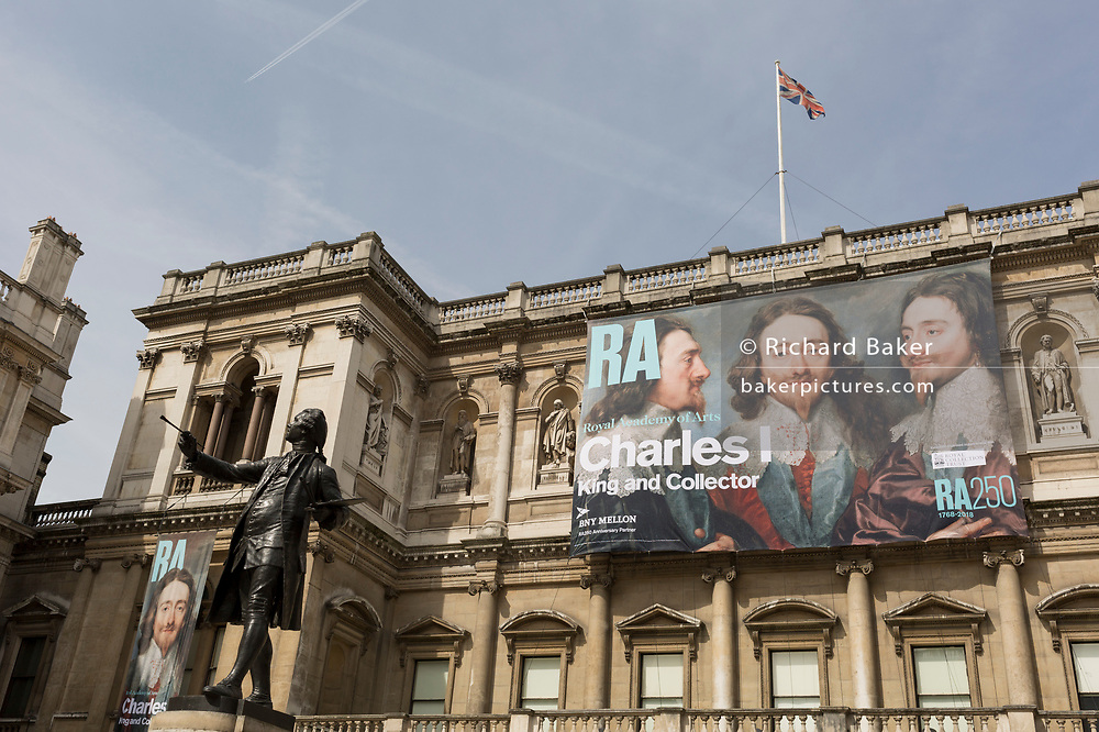"The statue of Sir Joshua Reynolds outside the Royal Academy in Piccadilly where the exhibition entitled 'Charles 1, King and Collector' is exhibited, on 6th April 2018, in London, England. This is a new cast of the original that was first exhibited outside the RA in 1904 and is an allegory of the human need for new challenges, of our instinct to always be scanning the horizon and the future. King Charles I amassed one of the most extraordinary art collections of his age, acquiring works by some of the finest artists of the past – Titian, Mantegna, Holbein, Dürer – and commissioning leading contemporary artists such as Van Dyck and Rubens. Following the his execution in 1649, the king's collection was sold off and scattered across Europe. Many works were retrieved during the Restoration, others now form the core of museums such as the Louvre and the Prado. This show reunites the greatest masterpieces of this magnificent collection for the first time. Sir Joshua Reynolds stands in the ""Annenberg Courtyard"" of Burlington House."