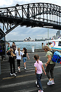 Mother and daughter (6 years old) and other children on Milsons Point wharf, with Sydney Harbour Bridge and Sydney Opera House in background. Sydney, Australia