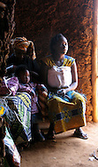 Kigali, Rwanda- A pair of Rwandan women and their children listen to a speaker in a church on the outskirts of Kigali. Churches like this one, affiliated with the Association des Églises Baptistes au Rwanda's (AEBR) Guardians of Hope project which helps people infected with HIV/AIDS to earn money by making traditional baskets to sell, play an important part in communities throughout Rwanda.
