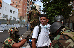 Members of the National Guard search and detain an  anti-government demonstrator after an  opposition march  to demand that President Chavez  submit to a recall referendum turned violent.  The march was held on the first day of the G15 summit in Caracas.