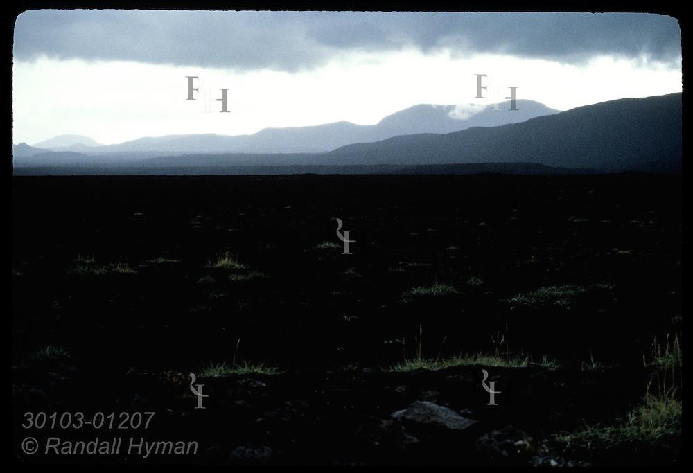 Endless expanse of black volcanic cinder carpets former pasture day after 1980 Hekla eruption. Iceland