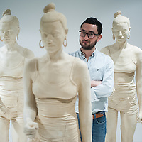 London, UK - 29 January 2014: artist Simon Fujiwara poses next to terracotta-dyed life sized plaster casts. His work Rebekkah, comprising 100 terracotta-dyed life sized plaster casts of a 16-year-old girl who took part in the 2011 London riots, goes on display at the Contemporary Art Society until 29 March.