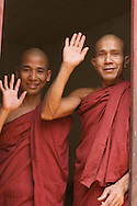 Friendly Burmese Buddhist monk wave goodbye in Mandalay, Myanmar.