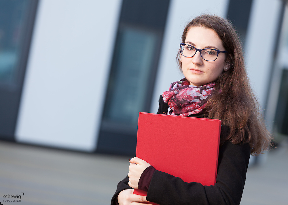 Austria, Vienna, Portrait of student with folder, close up