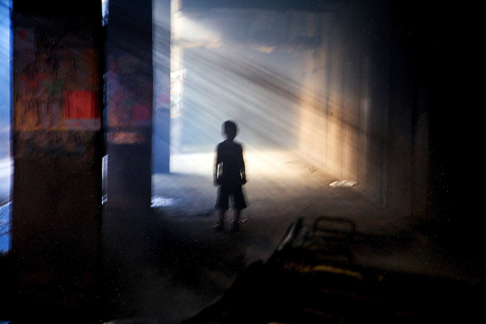 A young boy comes to investigate the scene of a garbage fire being tended to by Kosovo firefighters in an underground section of the Dardania neighborhood of Pristina, Kosovo. .