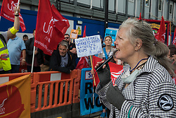 London, UK. 6th August, 2021. Dorothea Hackman of Stop HS2 and Hackney Food Bank addresses Unite members protesting outside the Euston construction site for the HS2 high-speed rail link regarding trade union access to construction workers building tunnel sections for the project. Unite claims that HS2's joint venture contractor SCS, formed by Skanska, Costain and Strabag, has been hindering 'meaningful' trade union access to HS2 construction workers in contravention of the HS2 agreement.