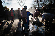 Some men scrape a dead pig's skin as women watch and help carrying water and other tools, in traditional way pig slaughtering. Legasa (Basque Country). January 7, 2017. The slaughter traditionally takes place in the autumn and early winter and the work often is done in the open. (Gari Garaialde / Bostok Photo)