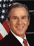 George Walker Bush (born 1946) 43rd President of the United States  2001-2009. 46th Governor of Texas  1995-2000.  Head-and-shoulders portrait with stars-and-stripes in background. American Politician Republican