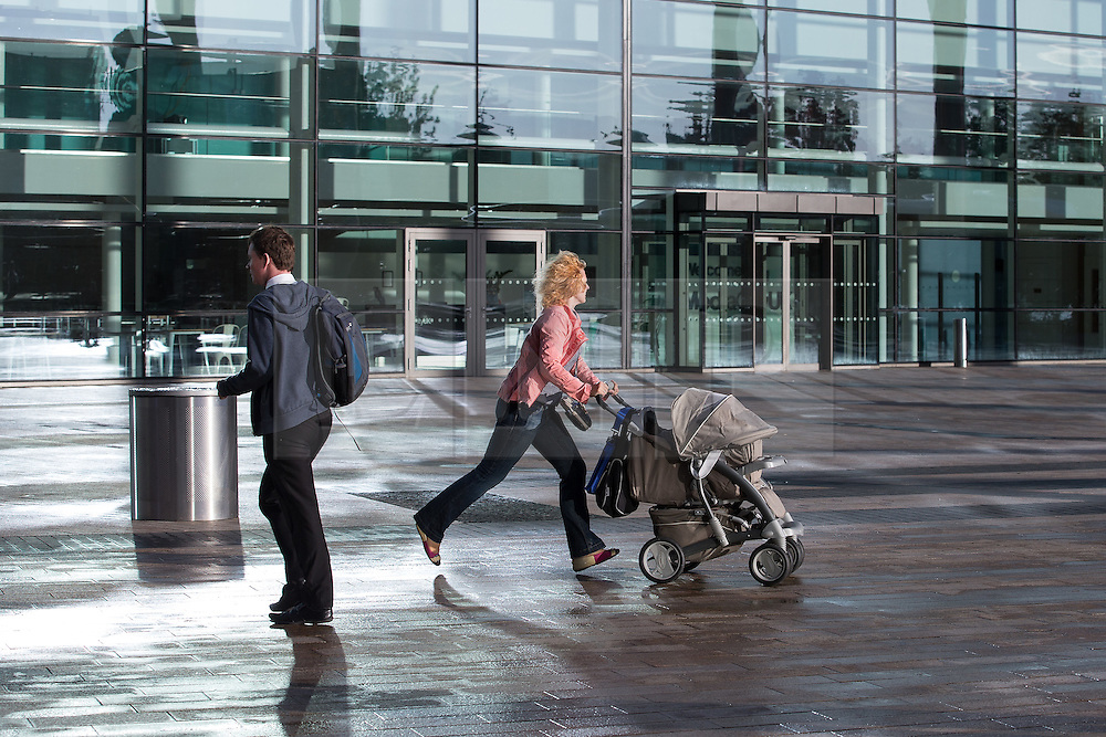 © Licensed to London News Pictures . 24/09/2014 . Media City , Salford , UK . A woman with a push chair runs for a tram . Autumn sunshine and big reflected light off the surface of glass buildings at Salford's Media City this morning as commuters travel to work  . Photo credit : Joel Goodman/LNP