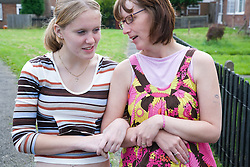Mother and teenage daughter walking down the street chatting,