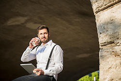 Businessman working on digital tablet and drinking coffee, Munich, Bavaria, Germany