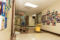 "James Moussette applies one of the six layers of wax to the floors of Elm Street School in preparation for the ""first day"" September 4th in the Laconia School District.  (Karen Bobotas/for the Laconia Daily Sun)"