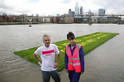 Art work by Ackroyd & Harvey made in grass with words by Ben Okri is set to float on the rising tide on the Thames on the 25th of June 2021, Central London, United Kingdom. The message is a call for action to save the planet from climate change catastrophe. Dan Harvey and Heather Ackroyd. The art work was moved by activists and laid onto a raft on the Thames as the tide was rising. The event marks the launch of XR Writers Rebel's Paint the Land project, which teams acclaimed writers and artists to create landscape graffitos drawing attention to the climate and ecological emergency. The Speakers at the event included the artist Ackroyd & Harvey, writer Ben Okri, Kelly Hill and Simon Bramwell, co-founder of Extinction Rebellion.  The event finished with a song by Damon Albarn and Mirabella Okra and the Capital Choir.