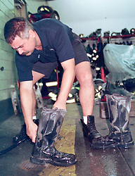 14 September 2001. New York, New York - USA.<br /> Post 9/11 World Trade Center attack.<br /> New York firefighter Dan Maurer washes the ash and dirt from his boots after an exhausting shift on site at the remains of the World Trade Center  <br /> Photo ©; Charlie Varley/varleypix.com
