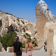 Tourists near huge rock in Goreme Open Air museum with cave churches, Cappadocia, Turkey