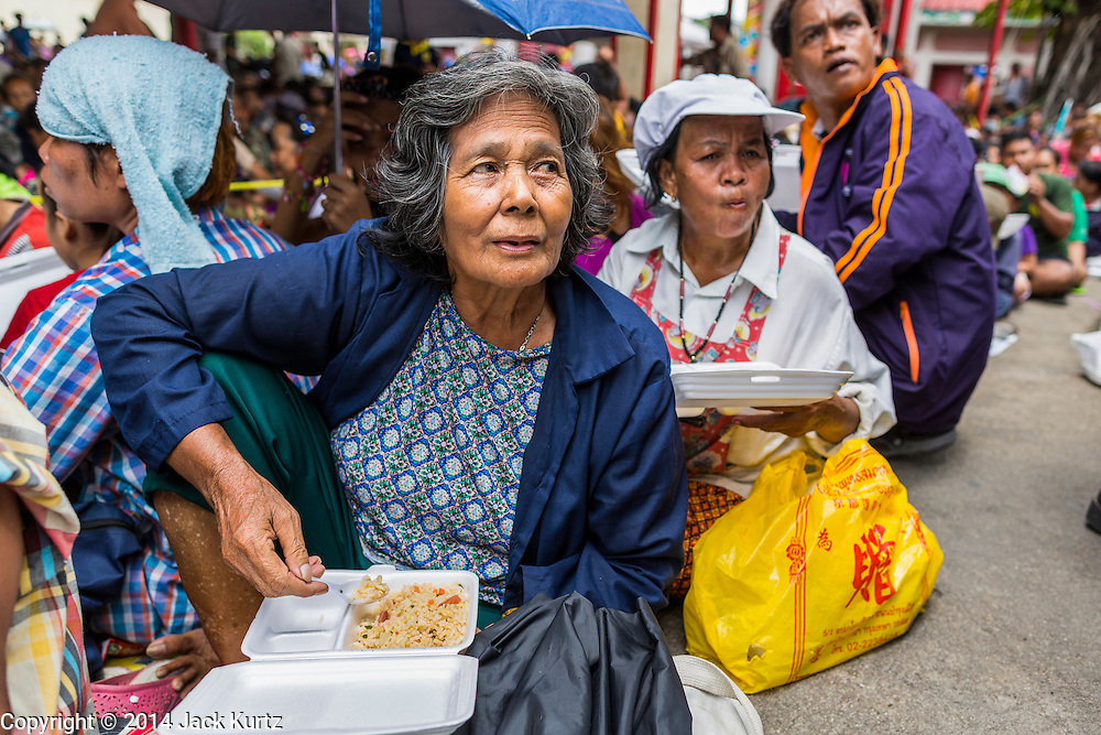 """09 AUGUST 2014 - BANGKOK, THAILAND: People eat chicken and basil during the community meal for Ghost Month at the Ruby Goddess Shrine in the Dusit section of Bangkok. The seventh month of the Chinese Lunar calendar is called """"Ghost Month"""" during which ghosts and spirits, including those of the deceased ancestors, come out from the lower realm. It is common for Chinese people to make merit during the month by burning """"hell money"""" and presenting food to the ghosts. At Chinese temples in Thailand, it is also customary to give food to the poorer people in the community.        PHOTO BY JACK KURTZ"""