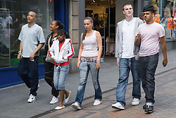 Multiracial group of teenagers walking down a street together,