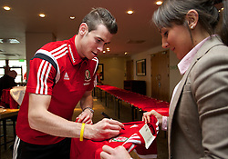 CARDIFF, WALES - Tuesday, March 4, 2014: Wales' Chris Gunter signs a shirt during a signing session at the St. David's Hotel ahead of the International Friendly against Iceland. (Pic by David Rawcliffe/Propaganda)  CARDIFF, WALES - Tuesday, March 4, 2014: Wales' xxxx during a training session at the Cardiff City Stadium ahead of the International Friendly against Iceland. (Pic by David Rawcliffe/Propaganda)
