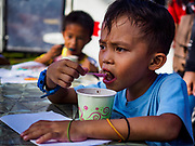"""26 JANUARY 2017 - MALILIPOT, ALBAY, PHILIPPINES: A boy who lives on the slopes of the Mayon volcano eats a """"champorado,"""" a Filipino sweet of sticky rice, coconut milk and chocolate, provided by the Philippine Red Cross in the shelter in Malilipot. The volcano was relatively quiet Friday, but the number of evacuees swelled to nearly 80,000 as people left the side of  the volcano in search of safety. There are nearly 12,000 evacuees in Santo Domingo, one of the communities most impacted by the volcano. The number of evacuees is impacting the availability of shelter space. The Philippines is now preparing to house the volcano evacuees for up to three months.    PHOTO BY JACK KURTZ"""