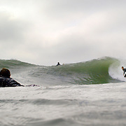 Surfers ride waves at Wrightsville Beach, NC