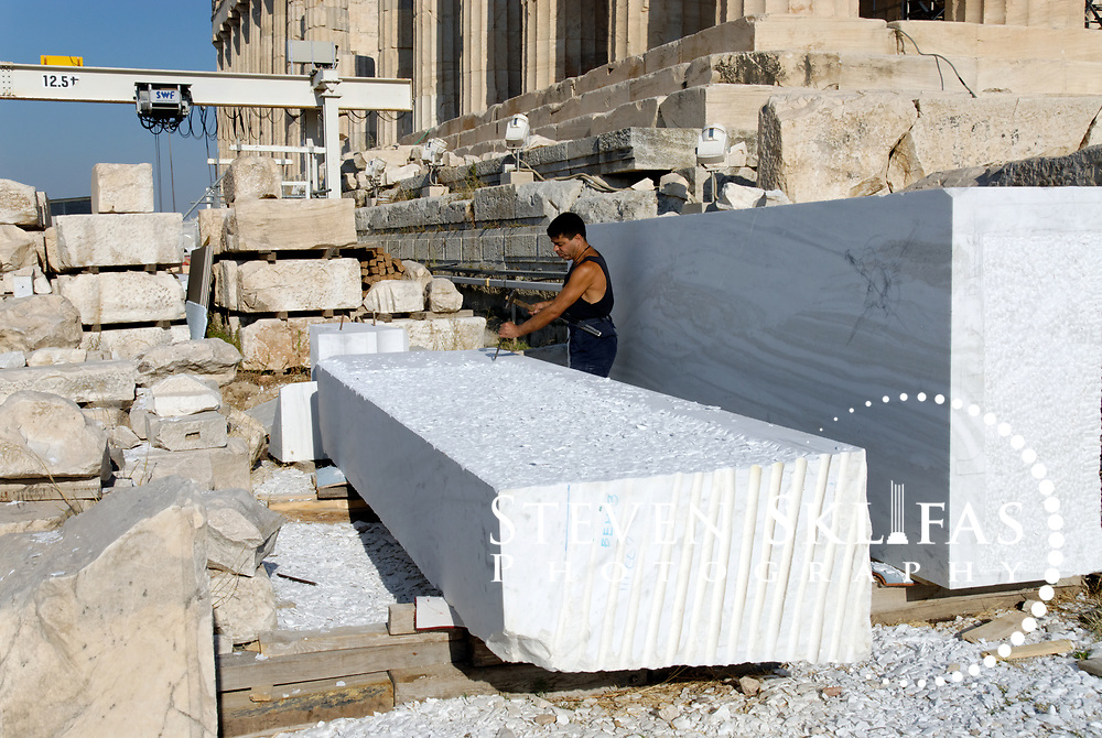 Acropolis. Athens. Greece. View of a work man, a modern marble sculptor picking or chiselling a large block of Pentelic marble as part of the Parthenon and Acropolis restoration project. The Acropolis of Athens and its monuments are a UNESCO World Heritage Site.