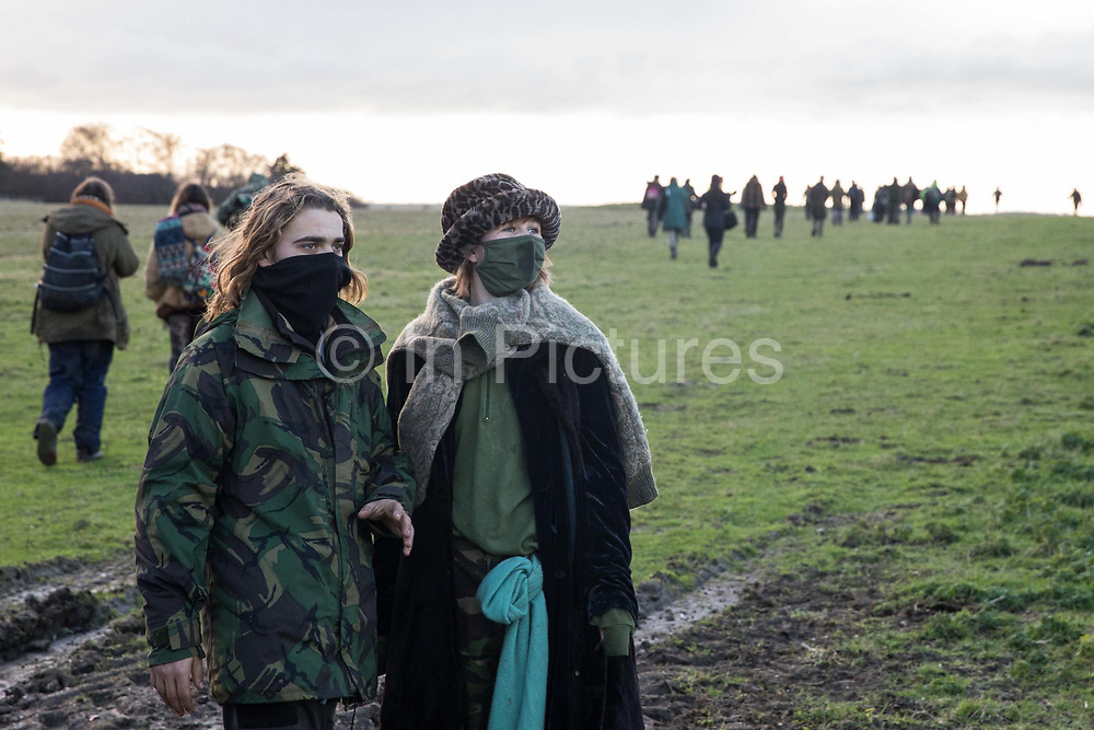 Over one hundred people, including local residents, climate and land justice activists and pagans, walk the route of the Stonehenge tunnel during a Mass Trespass at Stonehenge on 5 December 2020 in Salisbury, United Kingdom. The trespass was organised in protest against the approval by Transport Secretary Grant Shapps of a £1.7bn project for a two-mile tunnel beneath the World Heritage Site and a further eight miles of dual carriageway for the A303, as well as the government's £27bn Road Investment Strategy 2 (RIS2).