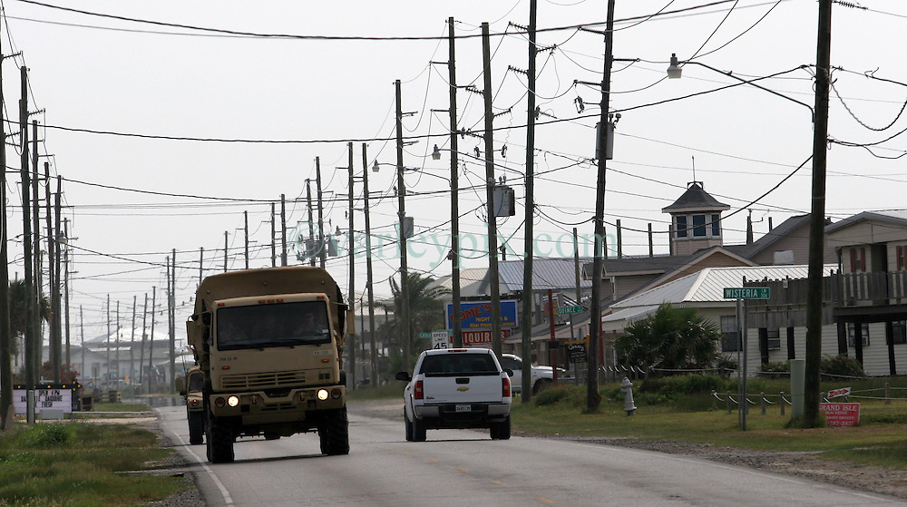 13 May 2010. Grand Isle, Lafourche Parish, Louisiana. <br /> Members of the Louisiana National Guard travel along Louisiana highway 1in Grand Isle as oil lands on the beaches of Jefferson and Lafourche parishes to the west of the Mississippi River outlet. Oil from the Deepwater Horizon catastrophe is evading booms laid out to stop it thanks in part to the dispersants which means the oil travels at every depth of the Gulf. <br /> Photo credit; Charlie Varley/varleypix.com