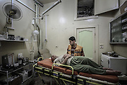 Dec. 29, 2015 - Aleppo, Syria - <br /> <br /> Syria Conflict<br /> <br /> Nour, a 18-year-old Syrian man, helps a wounded man in a hospital, in a rebel-controlled area of Aleppo, on December 29, 2015. Nour lost his leg following a bomb barrel attack by forces of Syria's President Bashar al-Assad near his house in Bustan al-Qasr district. A report from the Syrian Observatory for Human Rights (SOHR) claims that over 1,000 children have been killed in airstrikes during the nation'as ongoing civil war, an additional 1.5 million people have been wounded for life in the airstrikes that have been carried out by Syria'government since the Syrian conflict.<br /> ©Exclusivepix Media