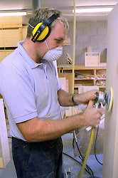Man with learning disability sanding wood,