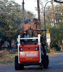 08 Sept 2005. New Orleans, Louisiana. Hurricane Katrina aftermath. <br /> Soldiers atop a bob cat drive along St Charles Ave.<br /> Photo; ©Charlie Varley/varleypix.com