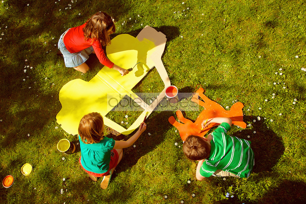 Children Painting Cardboard Cut Outs in Garden