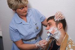 Nurse shaving patient,