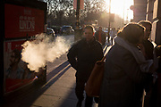 A man exhales a cloud of vape smoke in winter sunshine on Piccadilly, on 20th January 2020, in London, England.