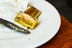 Small packets of butter on a plate.