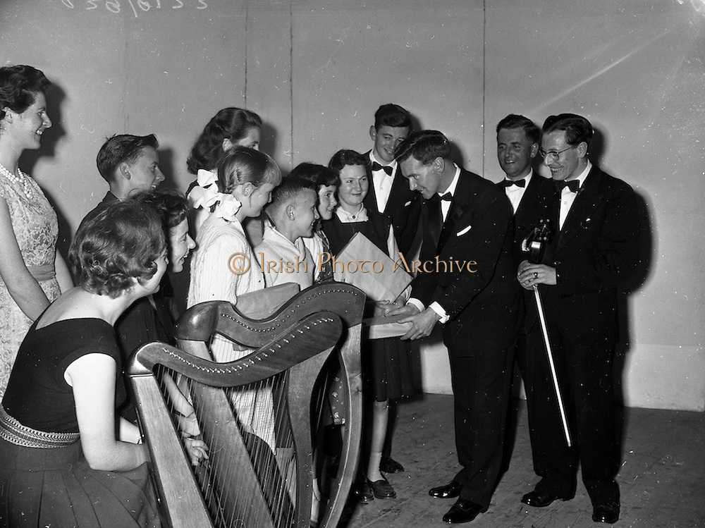 15/05/1959<br /> 05/15/1959<br /> 15 May 1959<br /> Gael Linn Competition at Listowel, Co. Kerry. Picture shows Diarmuid O'Broin, National Organiser, Gael-Linn presenting prizewinners with their prizes. Included are: R.E. singers and harpists, Kathleen Watkins; Deirdre Ni Faloinn; Breandan O'Ciobhain; Breandan O'Dubhaill and Sean Maguire, traditional fiddler. Prize-winners C. O'Cearbail; E. Ni Scanlain and M. Ni Dhuinn of Listowel; E. Ni, Gearailt, Tralee; D. Ni Gealbhain, Lynaw (Lixnaw ?) and S. O'Maoilmhichil, Ballylongford.
