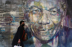 """South Africa - Cape Town - 17 June 2020 - Lady walk past a Mural of Nelson Mandela as we celebrate Mandela Day tomorrow. Nelson Mandela International Day (or Mandela Day) is an annual international day in honour of Nelson Mandela, celebrated each year on 18 July, Mandela's birthday. The day was officially declared by the United Nations in November 2009. Picture"""" Brendan Magaar/African News Agency(ANA)"""