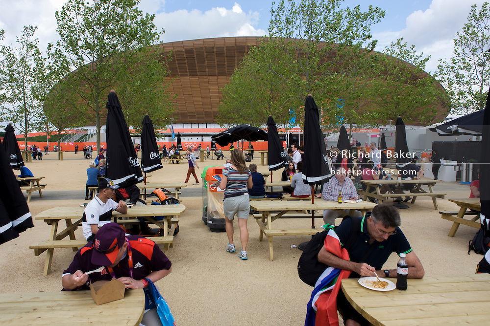 Spectators dine outside on tressle tables near the £105m Siberian Pine Velodrome curved roof during the London 2012 Olympics. Located in the north of the Olympic Park, the Velodrome is one of the most sustainable and iconic venues of the London 2012 Games. Sustainable choices have been made wherever possible; from the sourcing of wood certified by the Forest Stewardship Council used on the track and external cladding, to the installation of a 100% naturally ventilated system that eliminates the need for air conditioning. This land was transformed to become a 2.5 Sq Km sporting complex, once industrial businesses and now the venue of eight venues including the main arena, Aquatics Centre and Velodrome plus the athletes' Olympic Village.