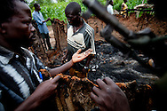 """Patrolling """"arrow boys"""" inspect a house burnt down by the LRA outside of Tambura on May 23, 2010. The """"arrow boys"""" are a self defence force that hs sprung up in Western Equatoria to defend against the LRA."""